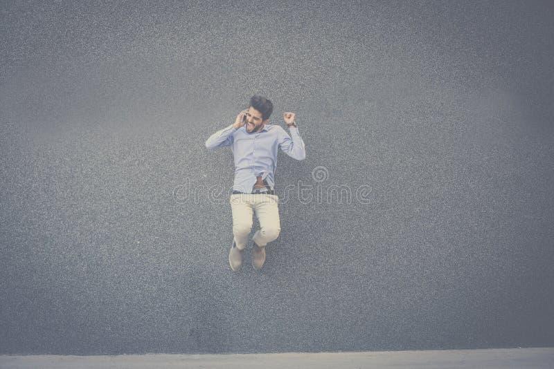 Hombre de negocios feliz que salta y que habla en el teléfono elegante imagen de archivo