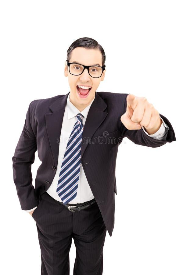Hombre de negocios feliz que señala hacia la cámara aislada en blanco detrás imagenes de archivo