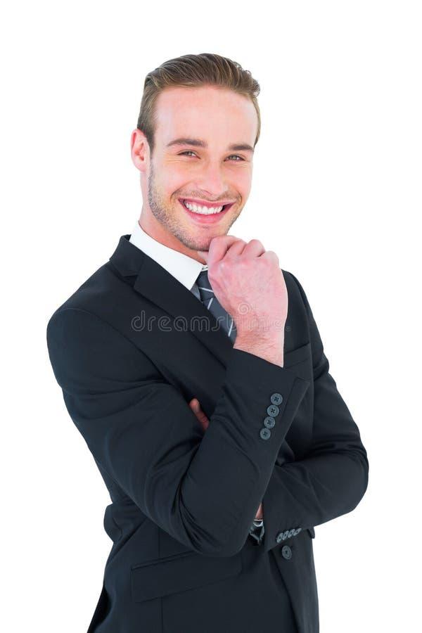 Hombre de negocios feliz que se coloca con la mano en la barbilla foto de archivo