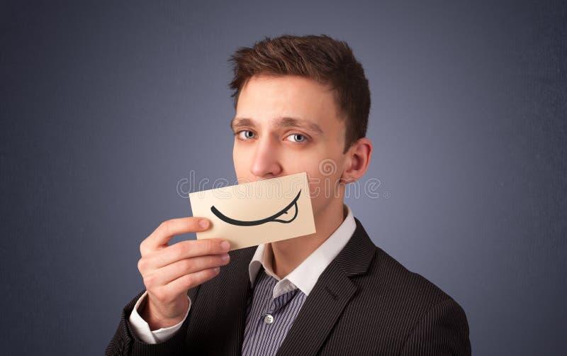 Hombre de negocios feliz que sostiene la tarjeta blanca divertida en su boca imagen de archivo