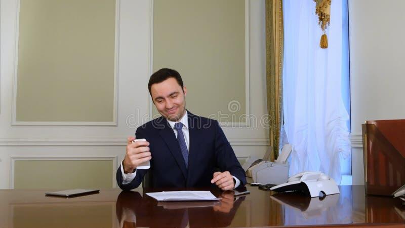 Hombre de negocios feliz que toma la foto del selfie con el teléfono móvil en oficina imagen de archivo libre de regalías