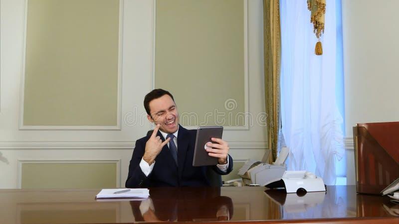 Hombre de negocios feliz que toma la foto del selfie con la tableta moderna y la sonrisa imagenes de archivo