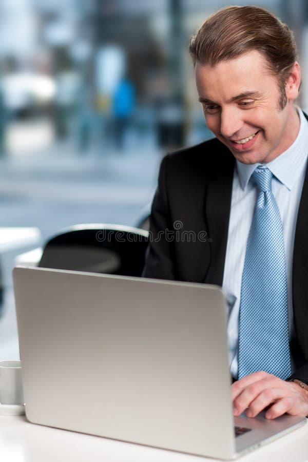 Hombre de negocios feliz que trabaja en el ordenador portátil foto de archivo