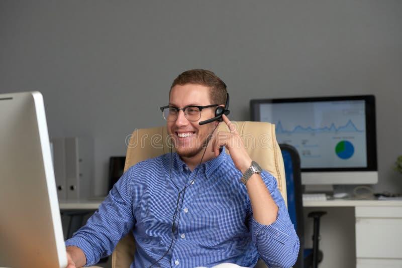 Hombre de negocios feliz que trabaja en oficina fotos de archivo