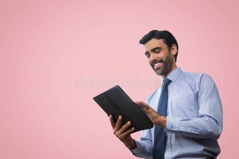 Hombre de negocios feliz que usa una tableta contra fondo rosado imagen de archivo libre de regalías