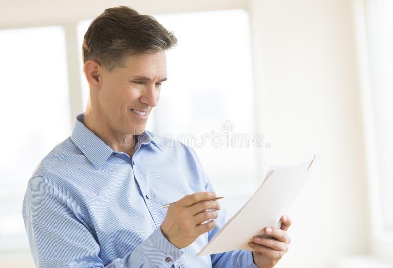 Hombre de negocios feliz Reading Document foto de archivo libre de regalías