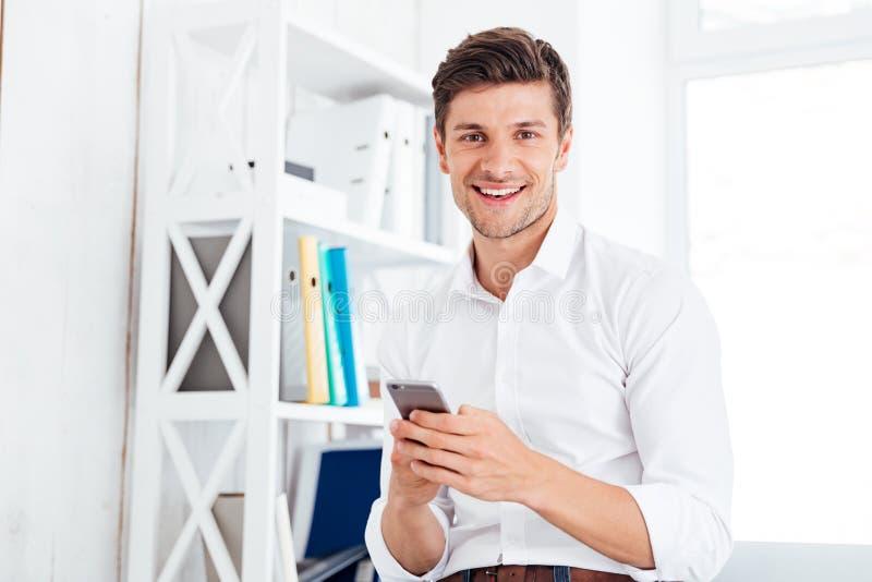 Hombre de negocios feliz sonriente que se sienta en la tabla y usar smartphone fotografía de archivo libre de regalías