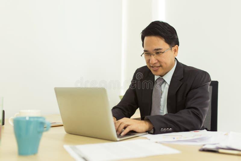 Hombre de negocios feliz usando el ordenador portátil en su escritorio de oficina imágenes de archivo libres de regalías