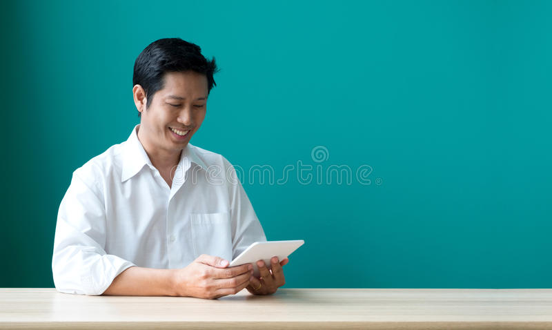 Hombre de negocios feliz usando la tableta en el escritorio en la oficina, succes imagen de archivo libre de regalías