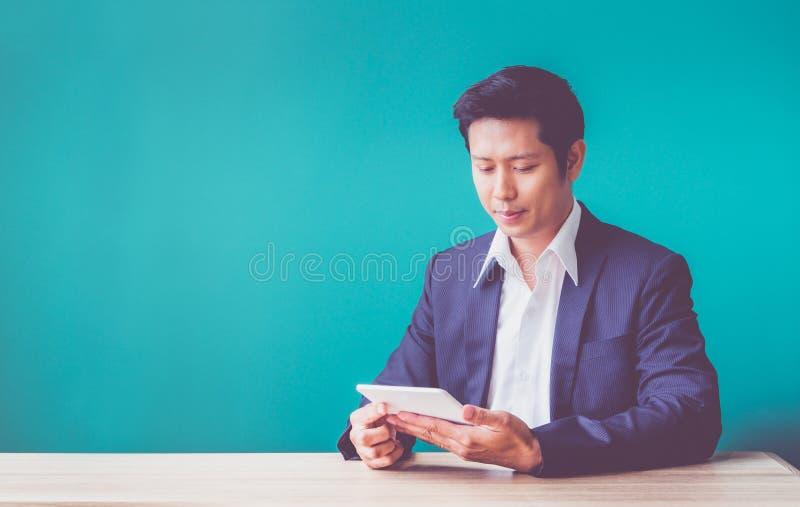 Hombre de negocios feliz usando la tableta en el escritorio en la oficina, succes imágenes de archivo libres de regalías