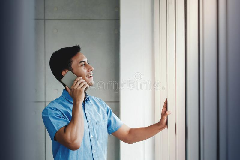 Hombre de negocios feliz Using Smartphone y hacer una pausa la ventana en oficina El hablar con alguien vía el teléfono móvil fotos de archivo
