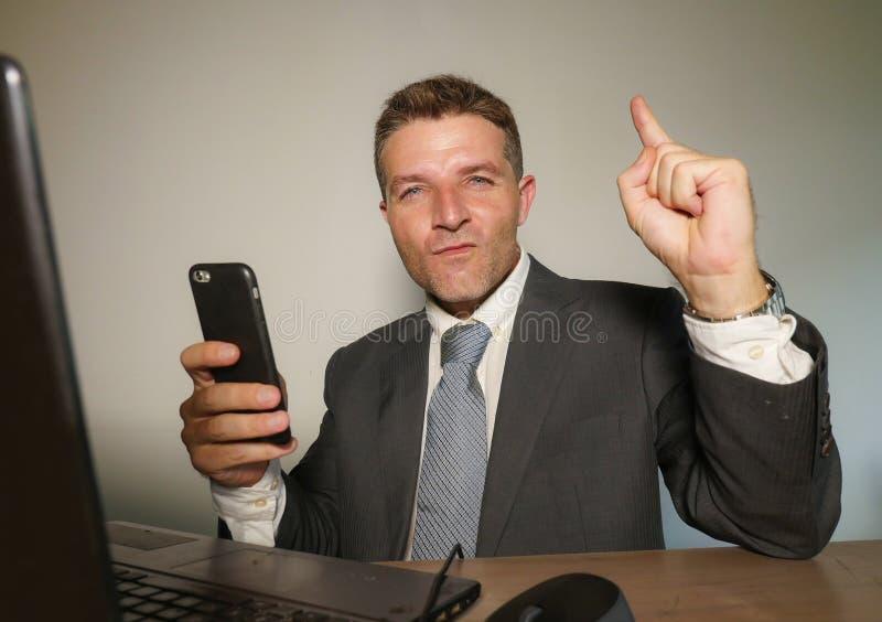 Hombre de negocios feliz y atractivo joven que trabaja con el teléfono móvil en el escritorio del ordenador de oficina que celebr foto de archivo libre de regalías
