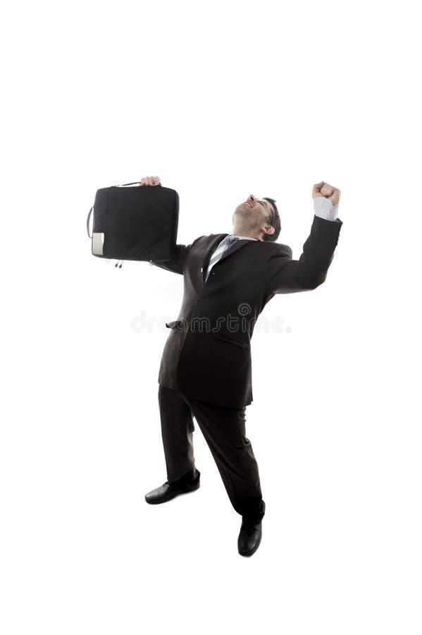 Hombre de negocios feliz y emocionado joven que sostiene la maleta que celebra la promoción y el éxito en el trabajo fotografía de archivo