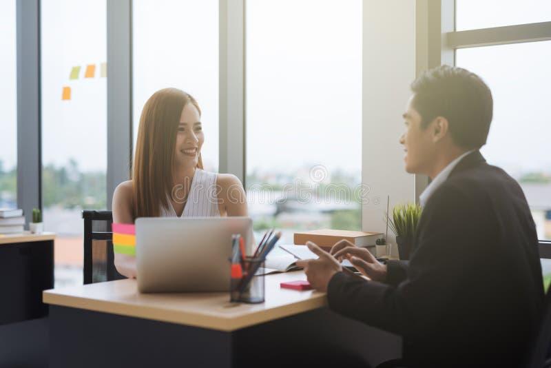 Hombre de negocios feliz y empresaria de los colegas del negocio que se sientan en un escritorio que habla en una oficina fotografía de archivo