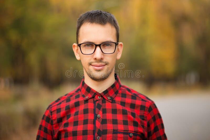 Hombre de negocios financiero joven hermoso en los vidrios que miran la cámara y que sonríen mientras que se coloca en parque imágenes de archivo libres de regalías