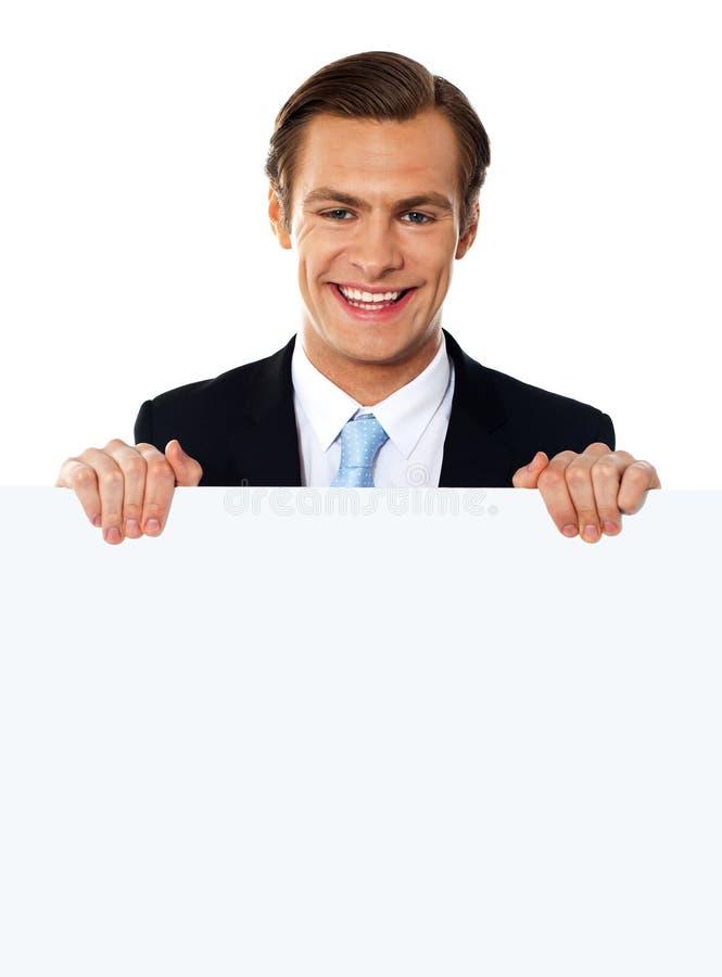Hombre de negocios fresco que sostiene un cartel en blanco imagen de archivo libre de regalías