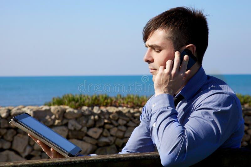 Hombre de negocios fresco que trabaja con la tableta y el teléfono al aire libre imagen de archivo libre de regalías
