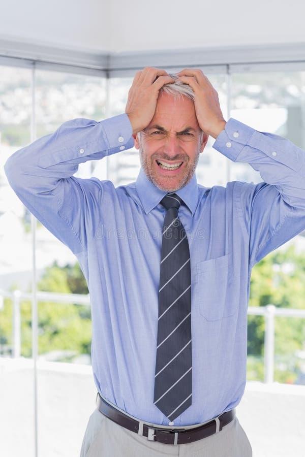 Hombre de negocios frustrado con las manos en su cabeza imagenes de archivo
