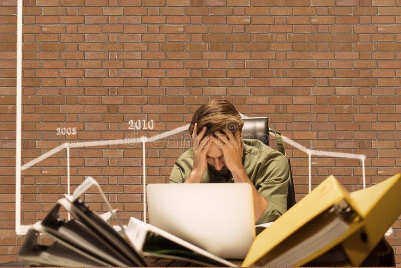 Hombre de negocios frustrado en un escritorio que se sienta contra la pared de ladrillo con los gráficos imagenes de archivo