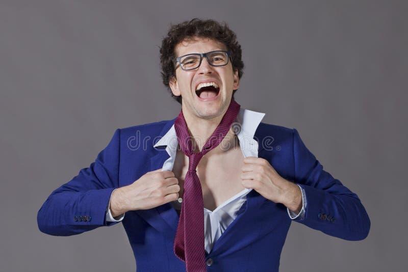Hombre de negocios frustrado Individuo joven con el pelo rizado, los vidrios y la chaqueta azul rasgando su camisa fotografía de archivo libre de regalías