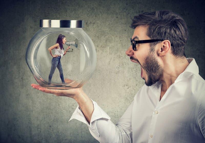 Hombre de negocios frustrado que sostiene un tarro de cristal con una mujer de griterío enojada atrapada en él imagen de archivo