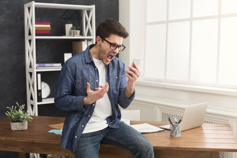 Hombre de negocios furioso que gesticula las manos y que grita en móvil foto de archivo