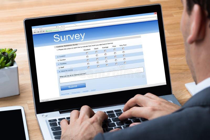 Hombre de negocios Giving Online Survey en el ordenador portátil imagenes de archivo