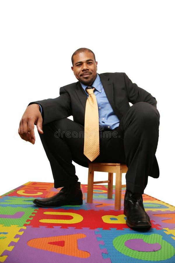 Hombre de negocios grande, pequeña silla fotografía de archivo libre de regalías