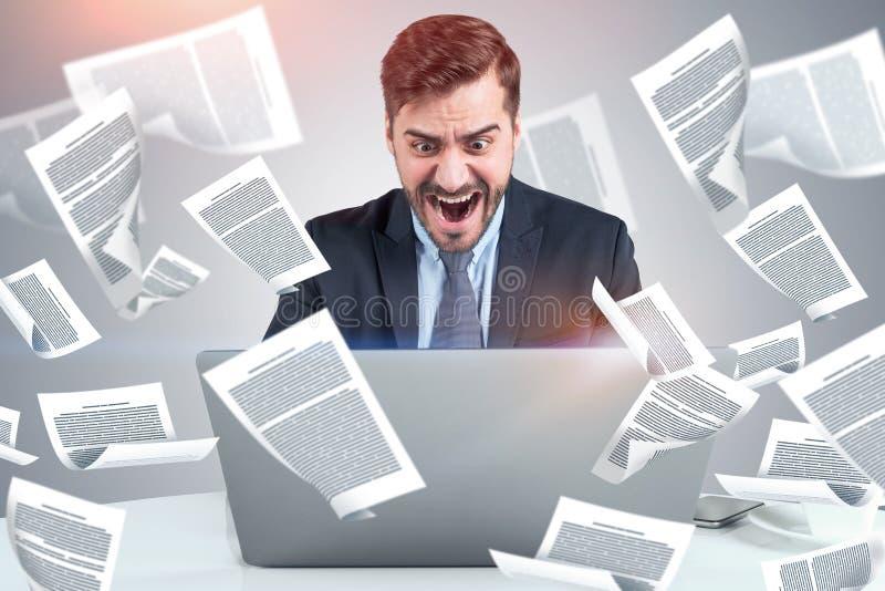 Hombre de negocios de grito con el ordenador portátil, documentos imagenes de archivo