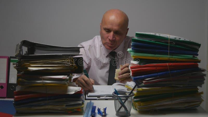 Hombre de negocios hambriento Eating del archivo de la oficina un bocadillo y escribir en trabajo del orden del día imagen de archivo libre de regalías