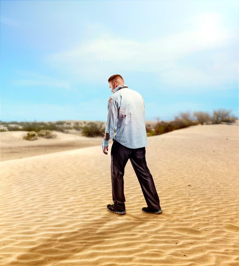 Hombre de negocios herido en el desierto fotos de archivo