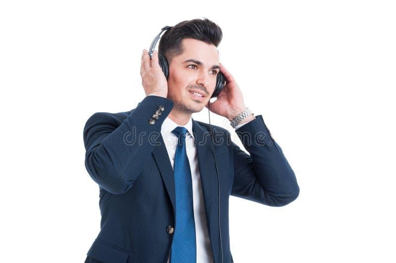 Hombre de negocios hermoso acertado que escucha y que disfruta de música encendido imagen de archivo libre de regalías
