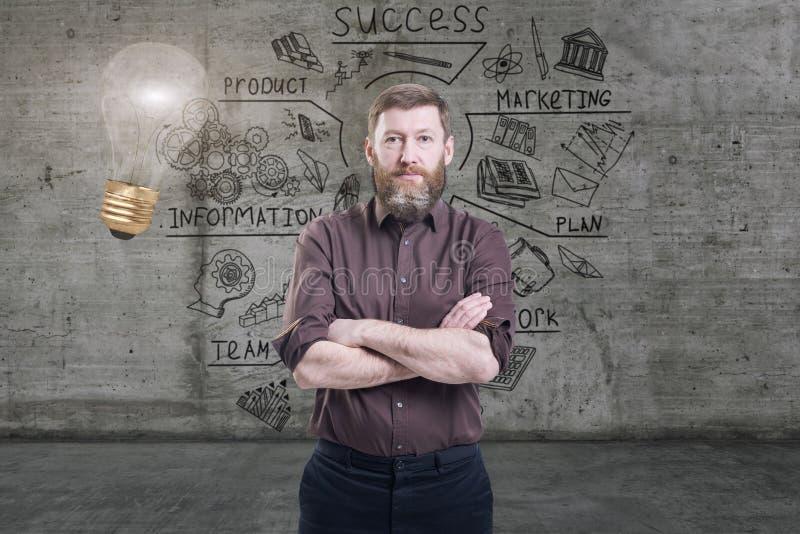 Hombre de negocios hermoso contra un muro de cemento con bosquejo dibujado en él y la bombilla brillante imagen de archivo