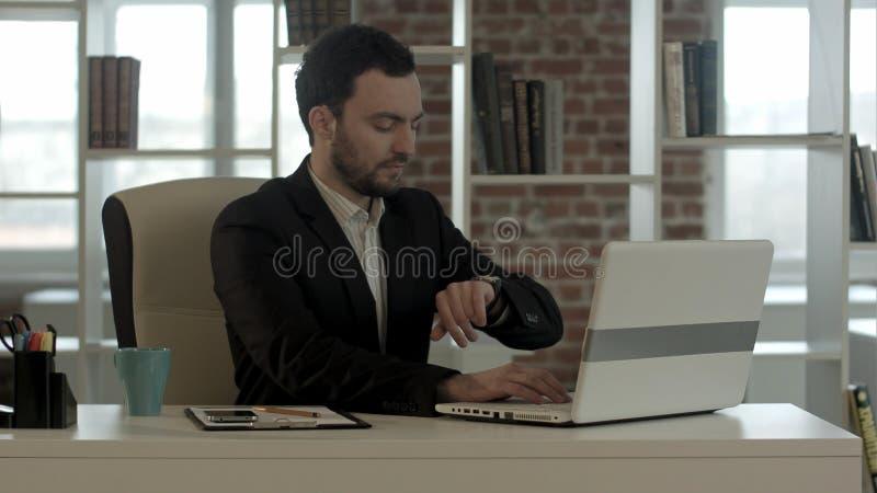 Hombre de negocios hermoso en el cuaderno del cierre de la oficina, funcionamiento de la parada fotografía de archivo libre de regalías
