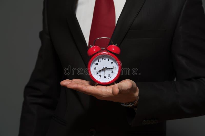 Hombre de negocios hermoso en el traje formal que sostiene el reloj imagenes de archivo