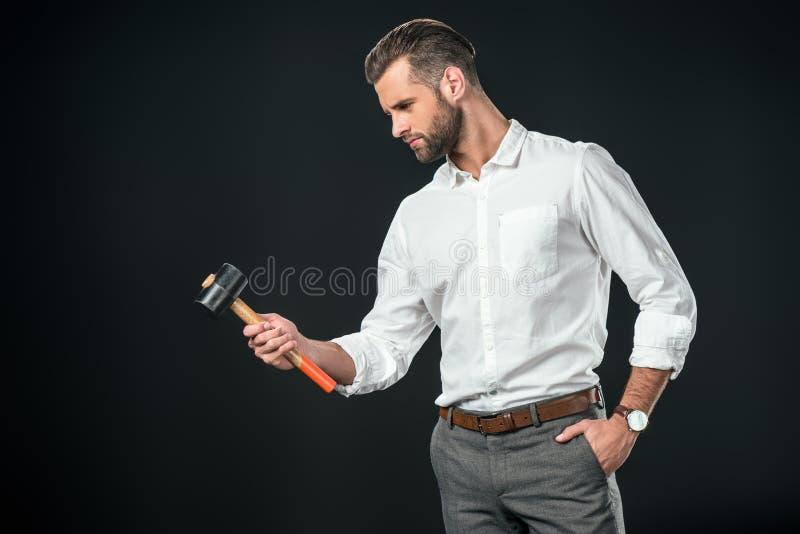 hombre de negocios hermoso en la camisa blanca que sostiene el martillo, fotografía de archivo