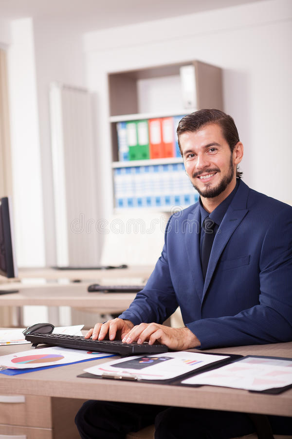 Hombre de negocios hermoso en traje en su oficina fotografía de archivo libre de regalías