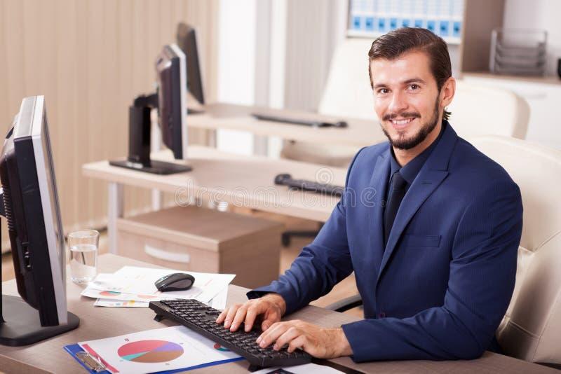 Hombre de negocios hermoso en traje en su oficina imágenes de archivo libres de regalías