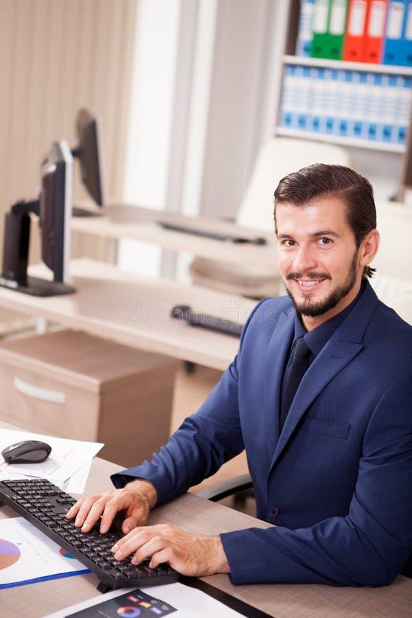 Hombre de negocios hermoso en traje en su oficina foto de archivo libre de regalías