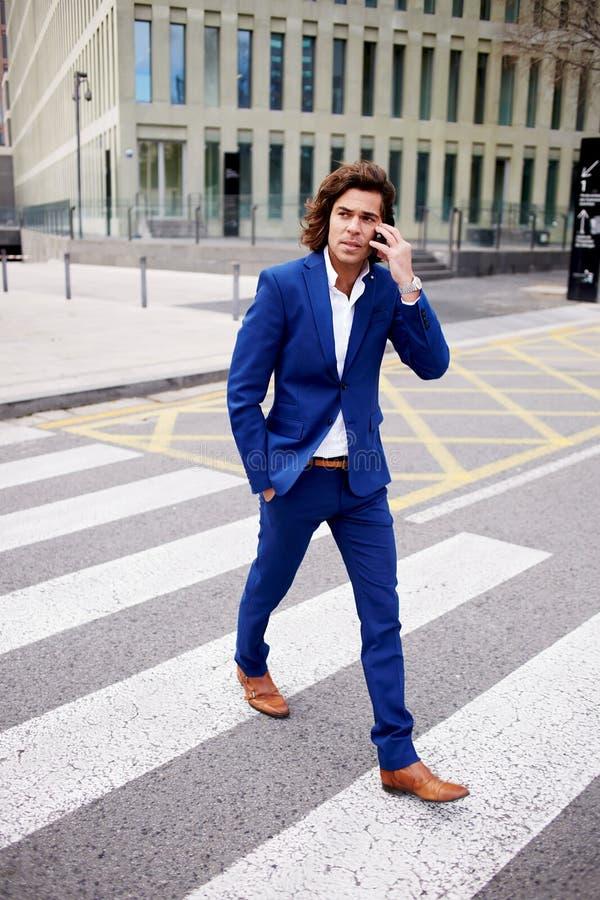 Hombre de negocios hermoso en un traje que habla en su teléfono elegante imagen de archivo libre de regalías