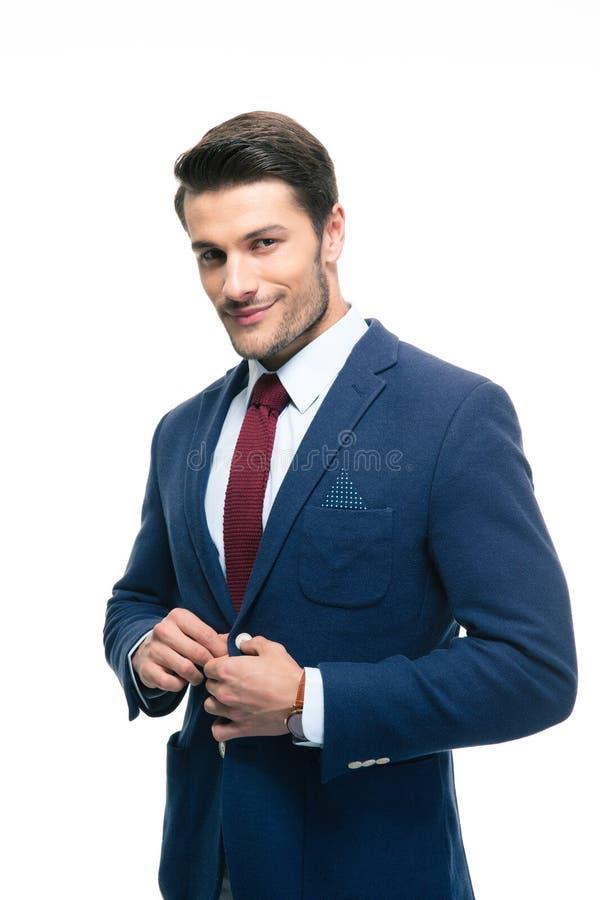 Hombre de negocios hermoso feliz que pone en la chaqueta del traje foto de archivo