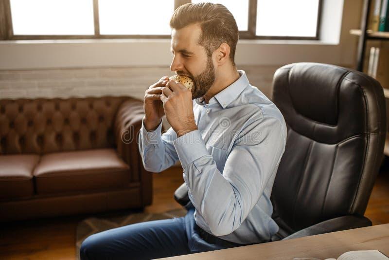 Hombre de negocios hermoso joven comer la hamburguesa en su propia oficina Él se sienta en la tabla y la comida de la mordedura D fotos de archivo libres de regalías