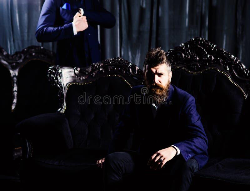 Hombre de negocios hermoso joven con la barba en el traje negro que se sienta en silla y que habla con el altavoz Colores retros  fotografía de archivo
