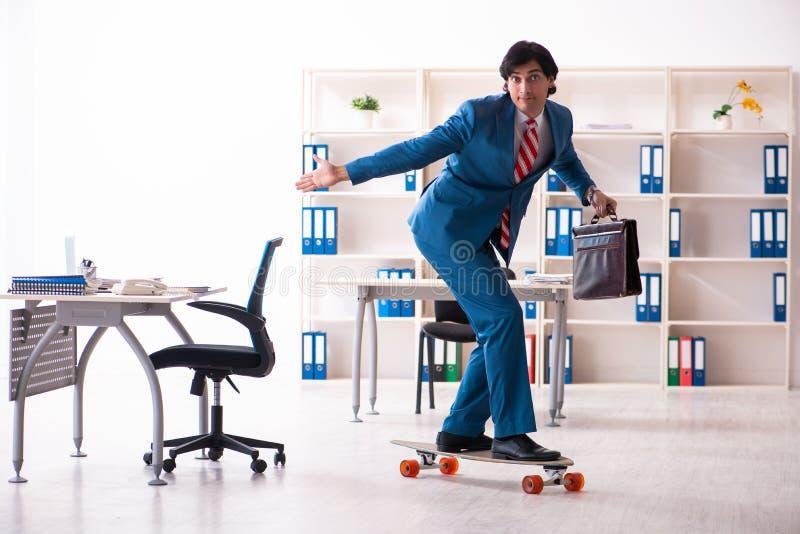 Hombre de negocios hermoso joven con longboard en la oficina fotos de archivo