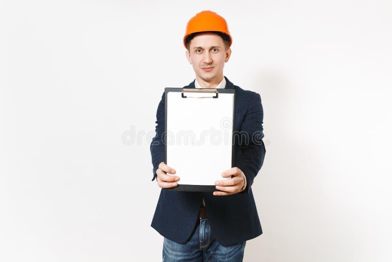 Hombre de negocios hermoso joven en el traje oscuro, casco de protección protector señalando el tablero con la hoja en blanco par imagen de archivo