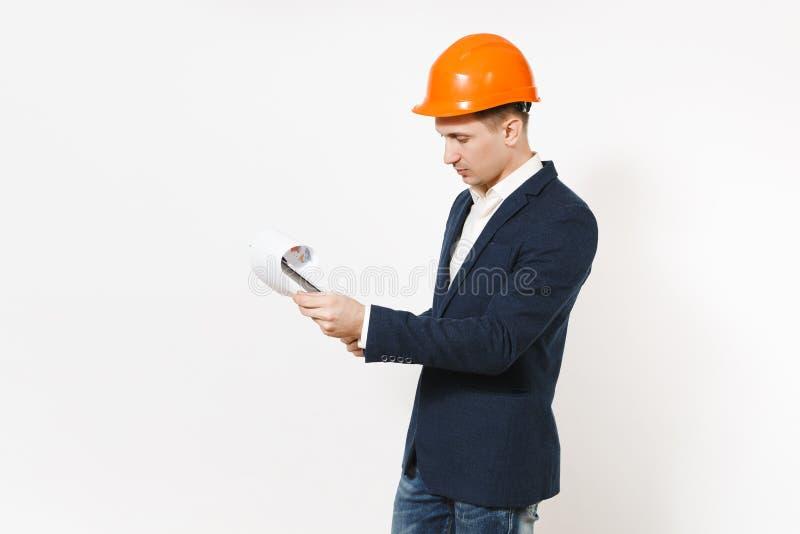 Hombre de negocios hermoso joven en el traje oscuro, casco protector de la construcción que mira en el tablero con el documento d imagen de archivo