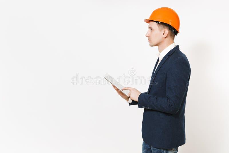 Hombre de negocios hermoso joven en traje oscuro, el casco de protección protector usando el ordenador de la PC de la tableta y l foto de archivo libre de regalías