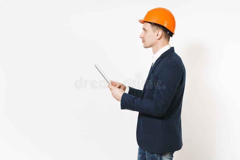 Hombre de negocios hermoso joven en traje oscuro, ordenador protector de la PC de la tableta de la tenencia del casco de protecci imagenes de archivo
