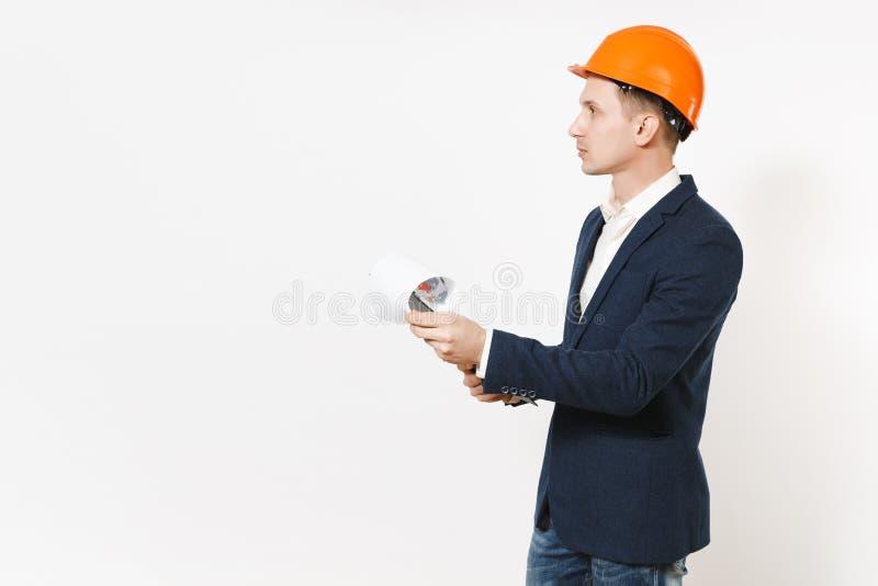 Hombre de negocios hermoso joven en traje oscuro, tablero protector de la tenencia del casco de protección con el documento y la  fotografía de archivo