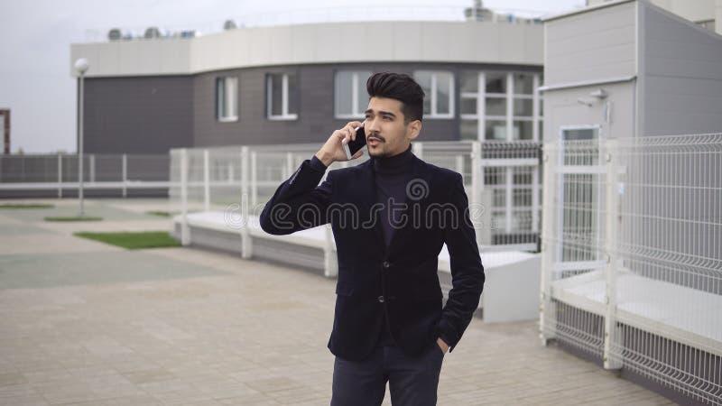 Hombre de negocios hermoso joven que camina y que habla en el teléfono móvil en la ciudad fotografía de archivo libre de regalías